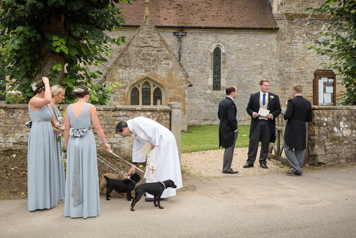 Vicar greeting dog flower girls for a wedding at Maidwell church in Northampton