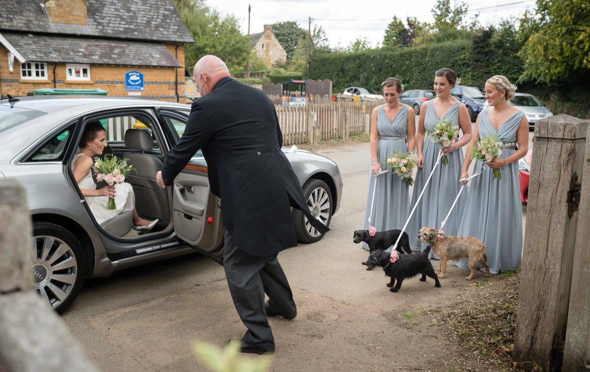 Bride being greeted by dog flower girls as she arrives at Maidwell church in Northampton