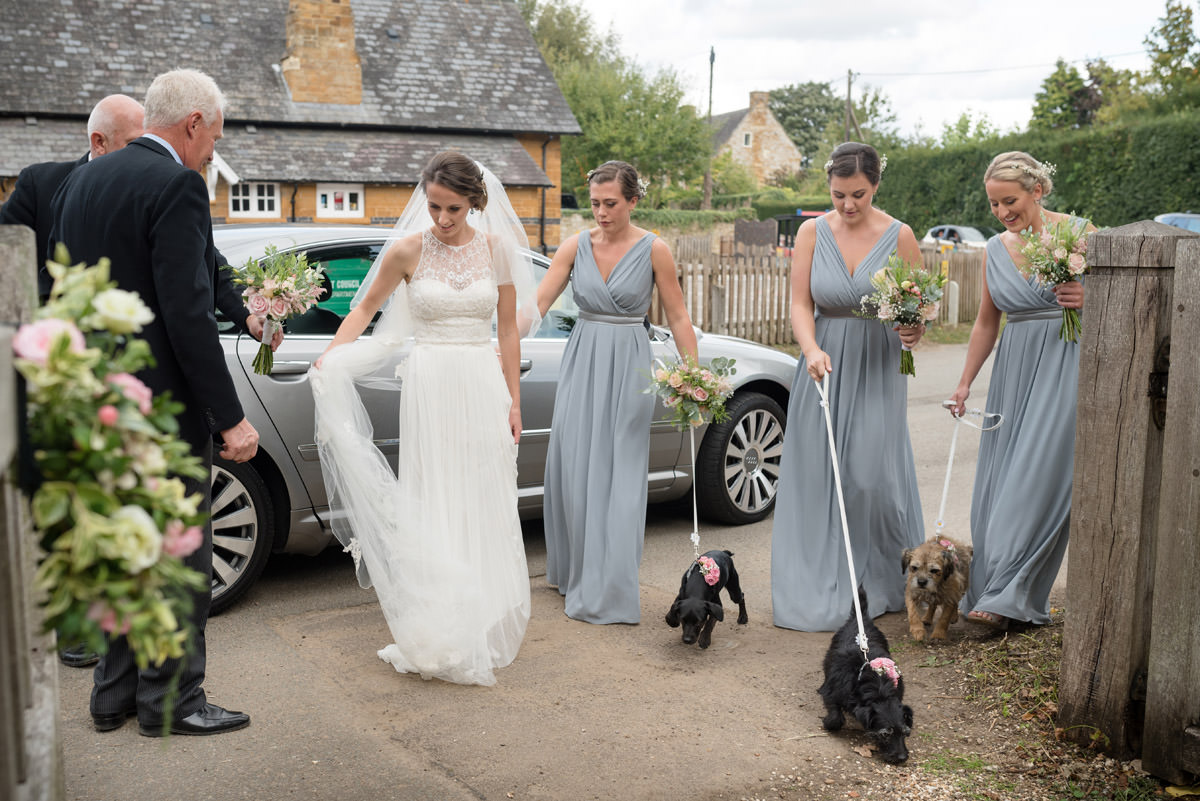 Bride, bridesmaids and dog flower girls arriving at Maidwell church in Northampton