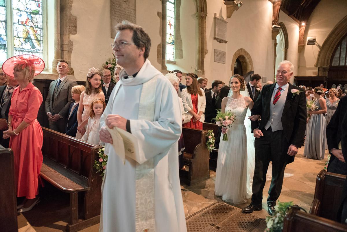Bride walking down the aisle at Maidwell church in Northampton