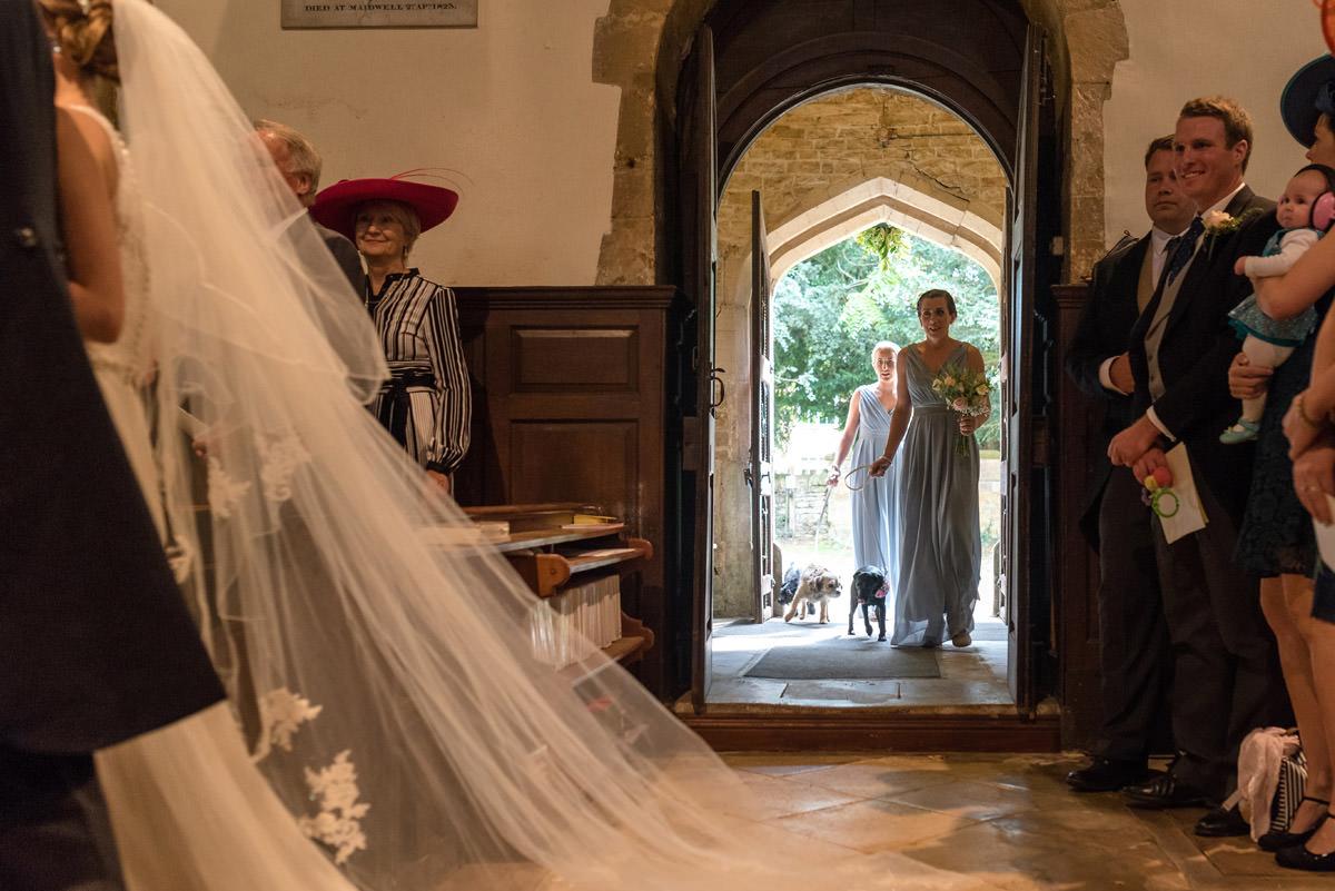 Bridesmaids and dog flower girls walking into Maidwell church in Northampton