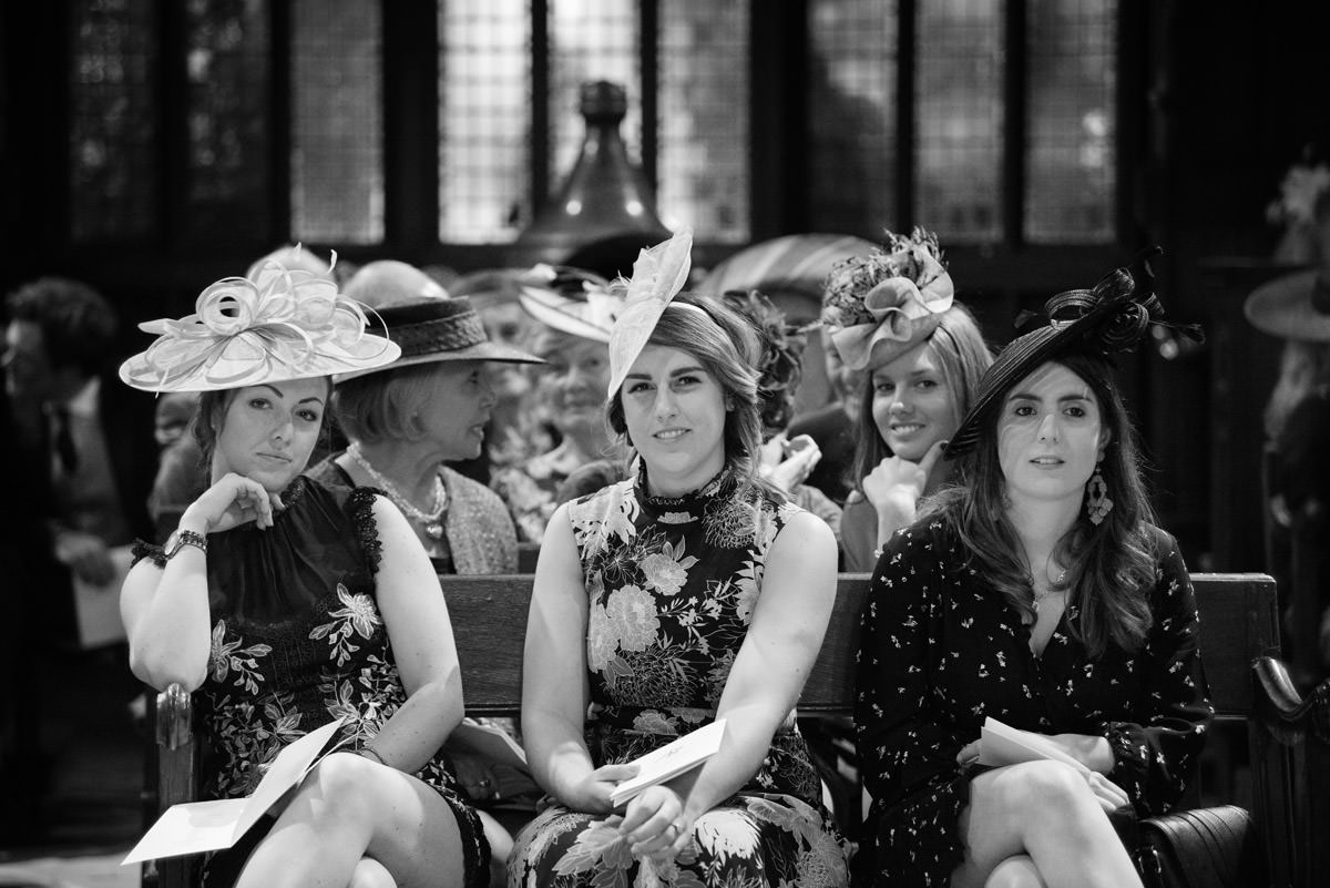 Three female wedding guests in hats in a row at Maidwell church in Northampton