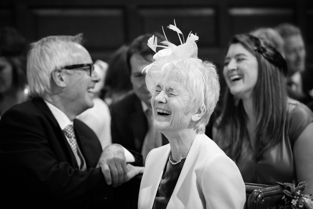 Wedding guests laughing during the signing of the register at Maidwell church in Northampton
