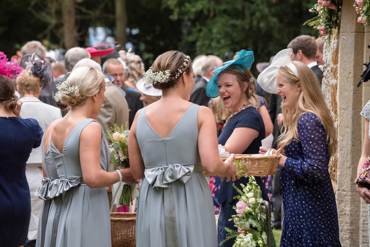 Bridesmaids handing out confetti at Maidwell church in Northampton