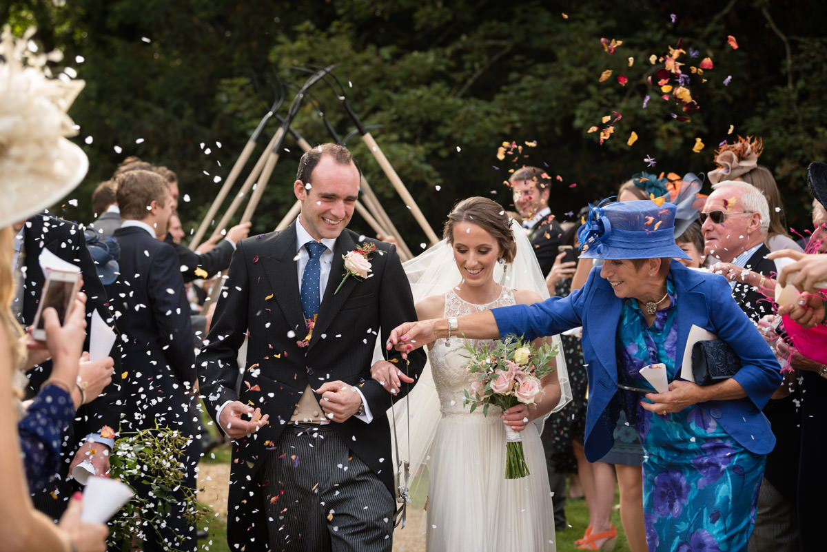 Wedding guest handing Bride a lucky horseshoe at Maidwell church in Northampton