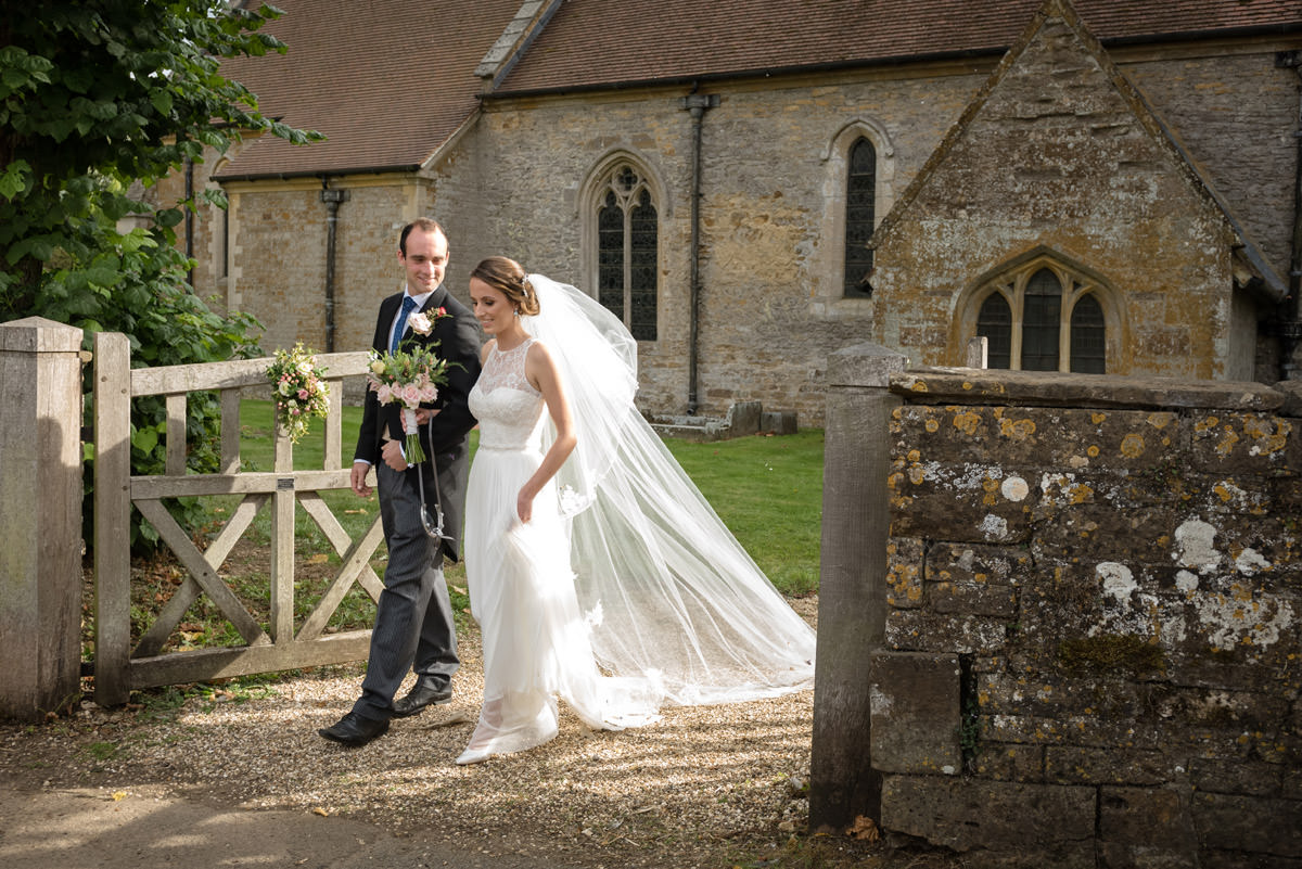 Bride & Groom walking out of Maidwell church in Northampton