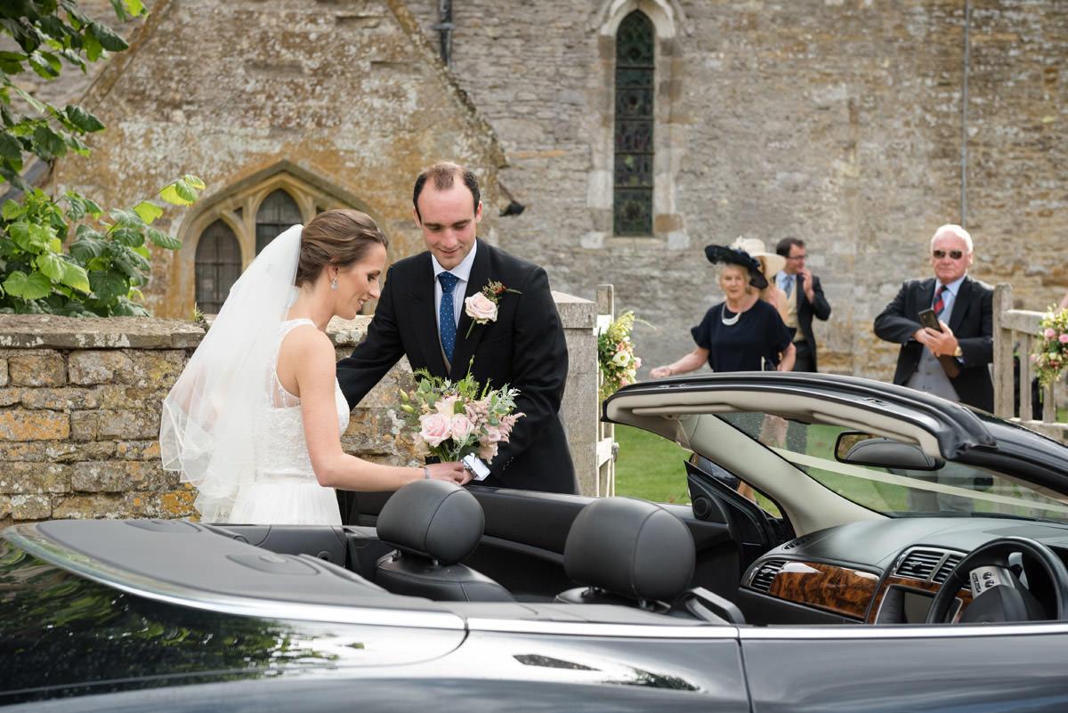 Groom helping Bride into their open top wedding car