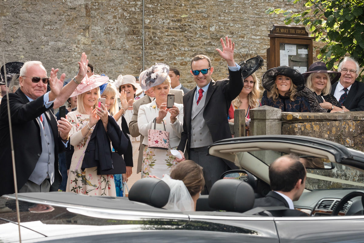 Guests waving as couple leave church in an open top sports car