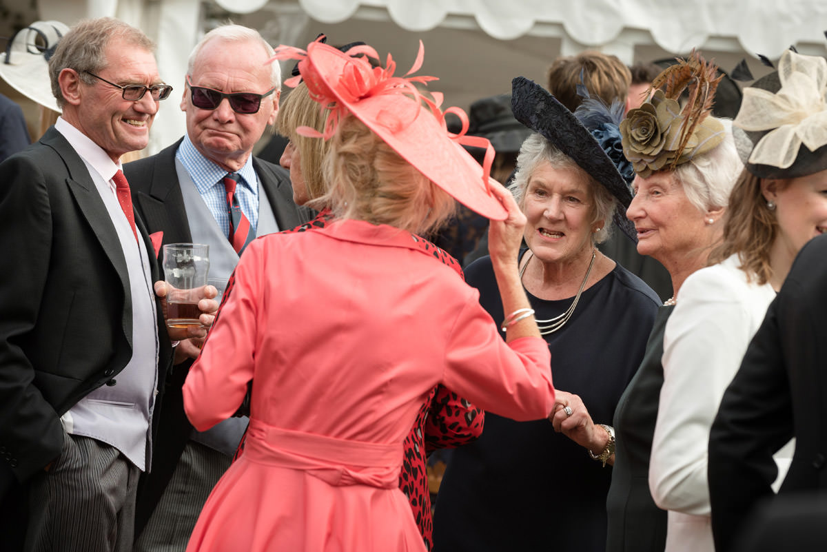Wedding guests in hats enjoying the drinks reception
