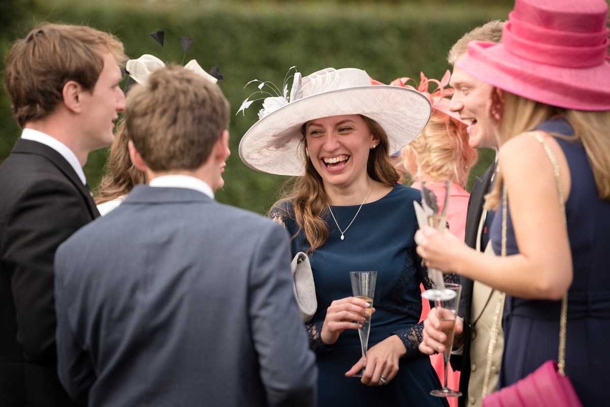 Female wedding guest laughing with friends during drinks reception