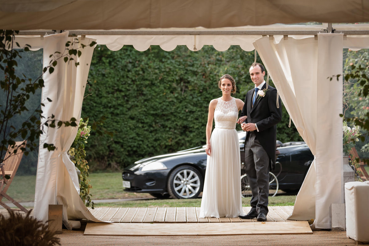 Bride and Groom waiting outside their marquee for dinner