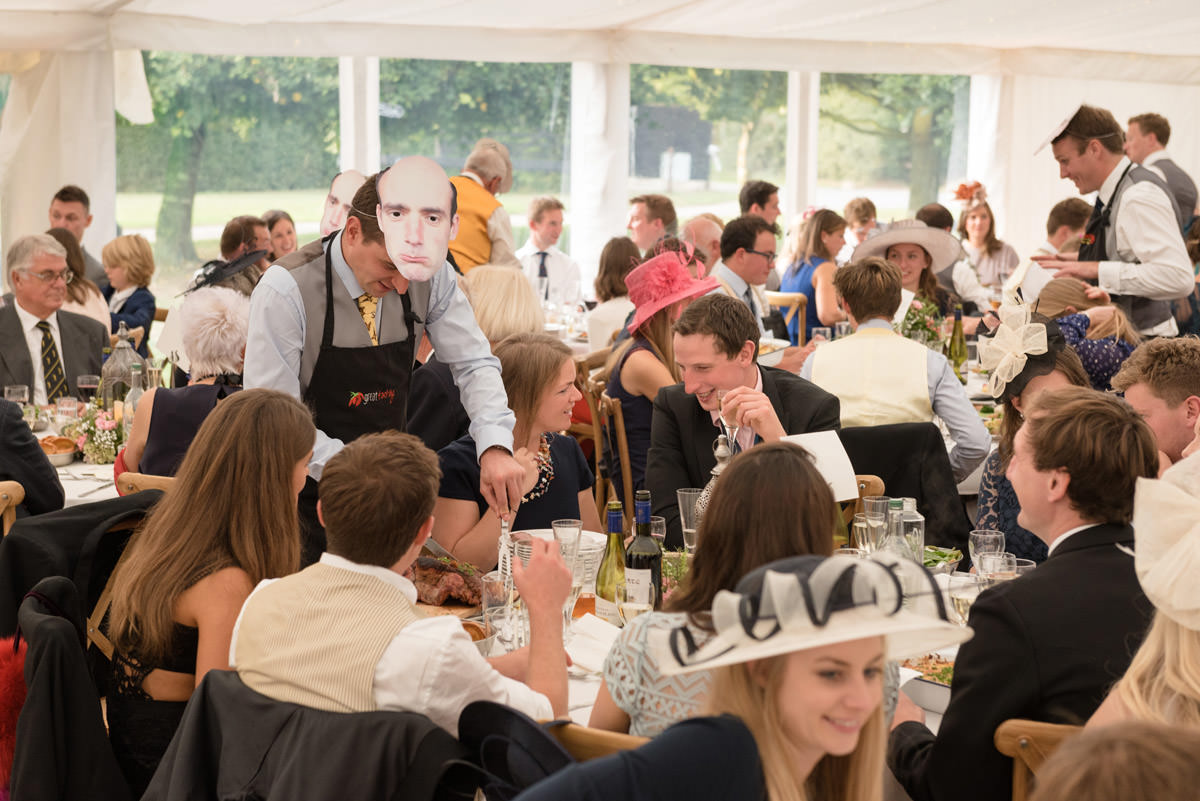 Guests carving roast dinner at a marquee wedding
