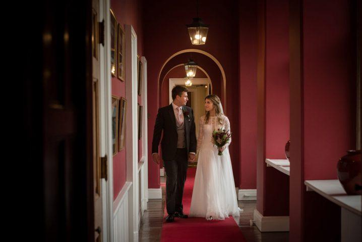 Bride & groom walking inside Rushton Hall in Northants