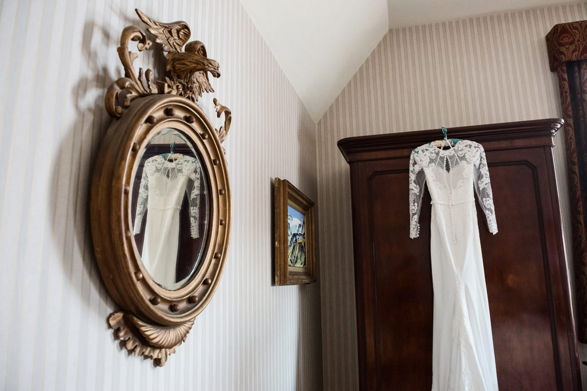 Mirror reflection of a wedding dress hanging on a wardrobe