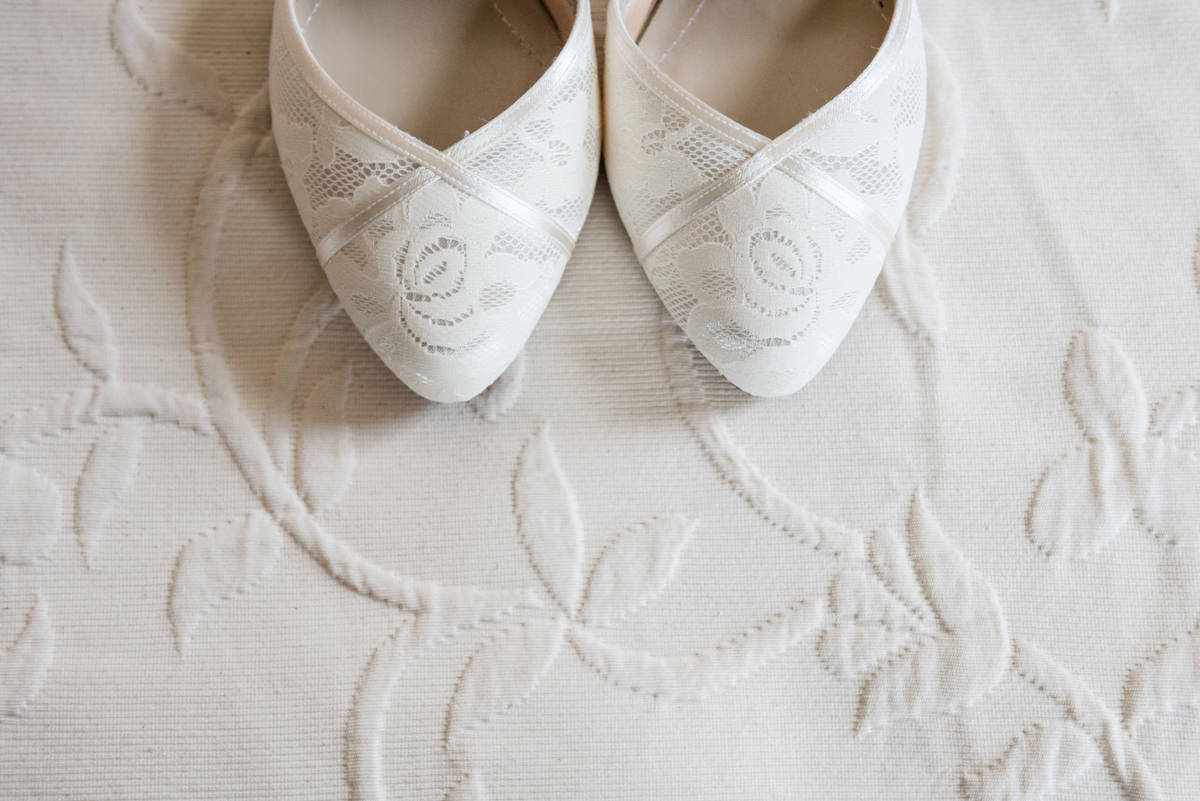 Wedding shoes with swirls on a bedspread with swirls
