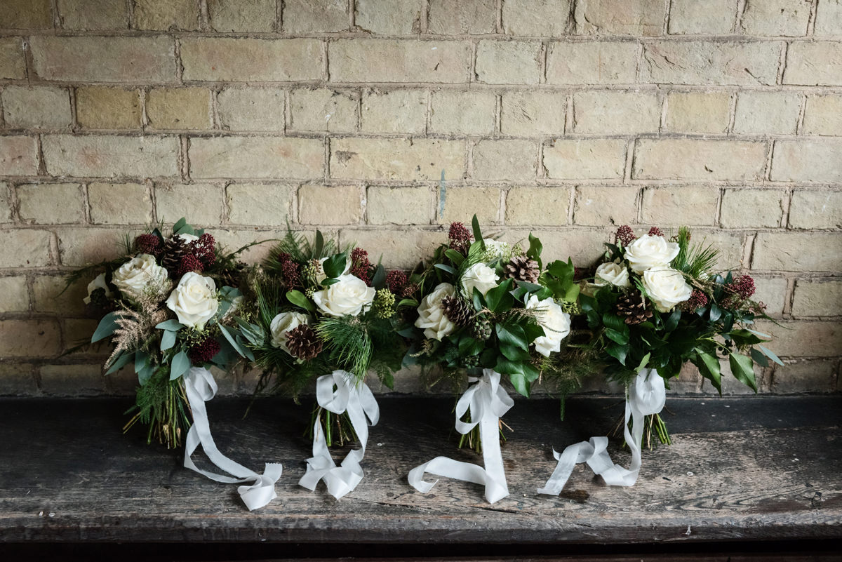 Four winter wedding bridesmaid bouquets with fir cones & silk ribbons