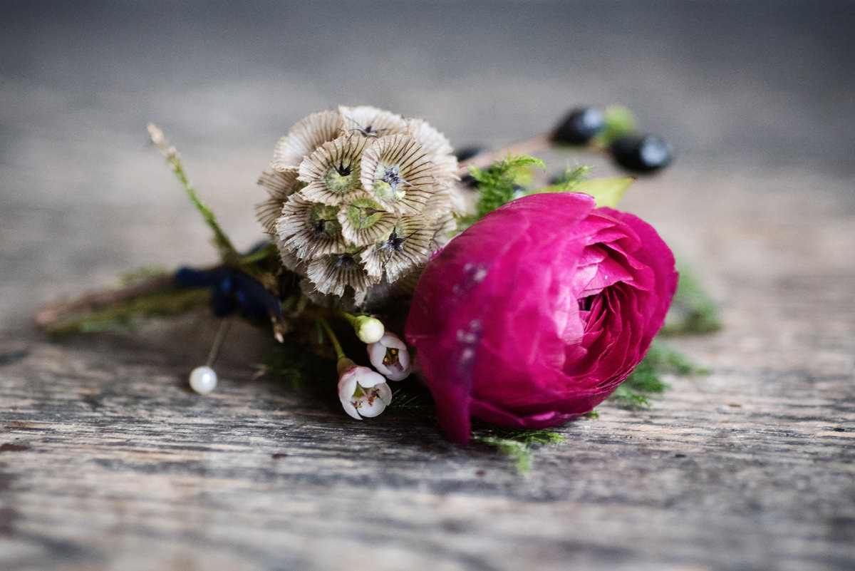 Winter wedding buttonhole with fuschia ranunculus