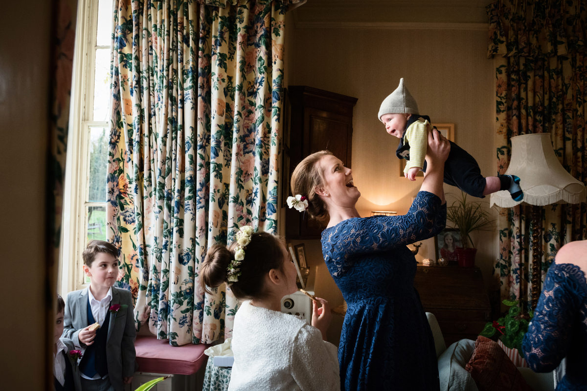 Bridesmaid playing aeroplanes with a young baby
