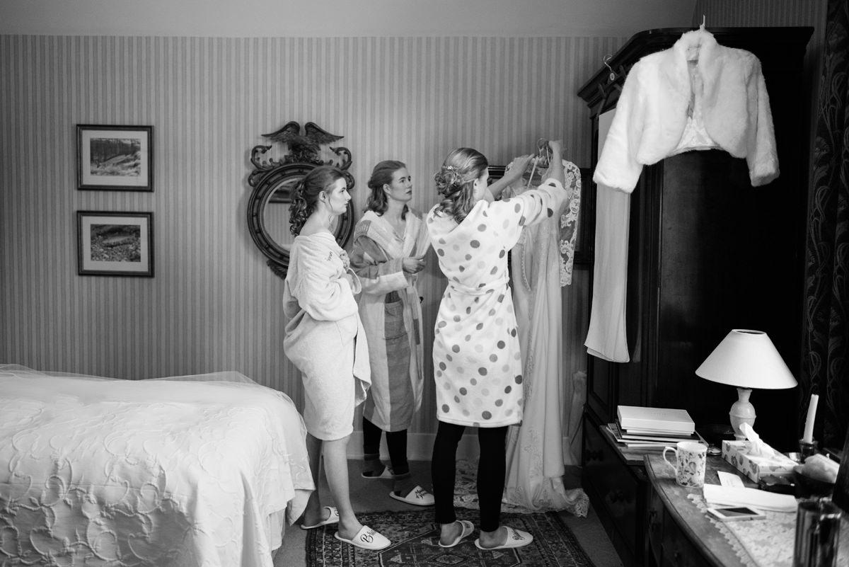 Bridesmaids helping the bride with her dress in Swavesey