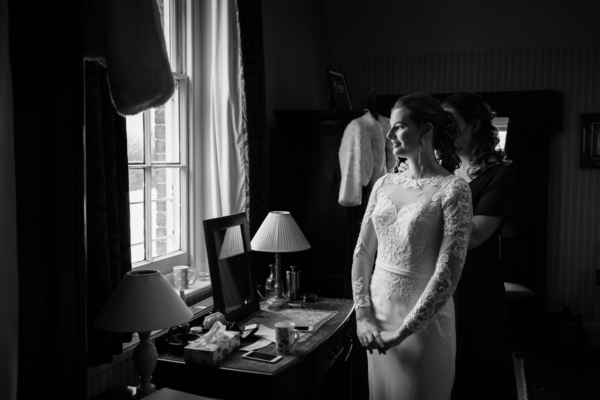 Bride looking out of the window while bridesmaid puts her necklace on in Swavesey