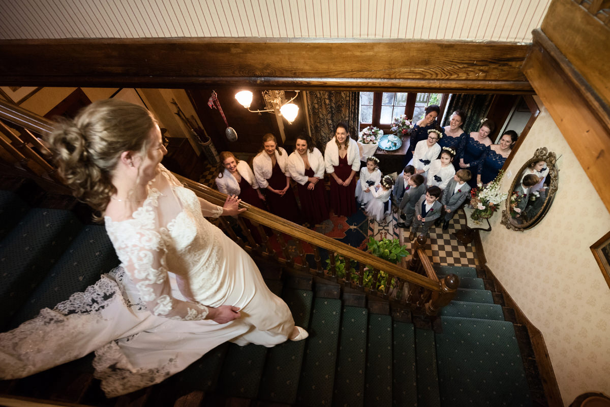 Bride coming down the stairs at home in Swavesey