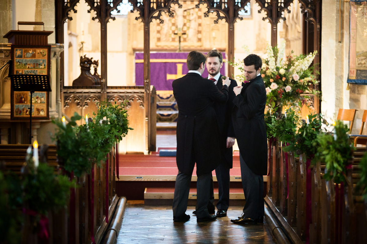 Groomsmen putting buttonholes on at St Andrew's church in Swavesey, Cambridge