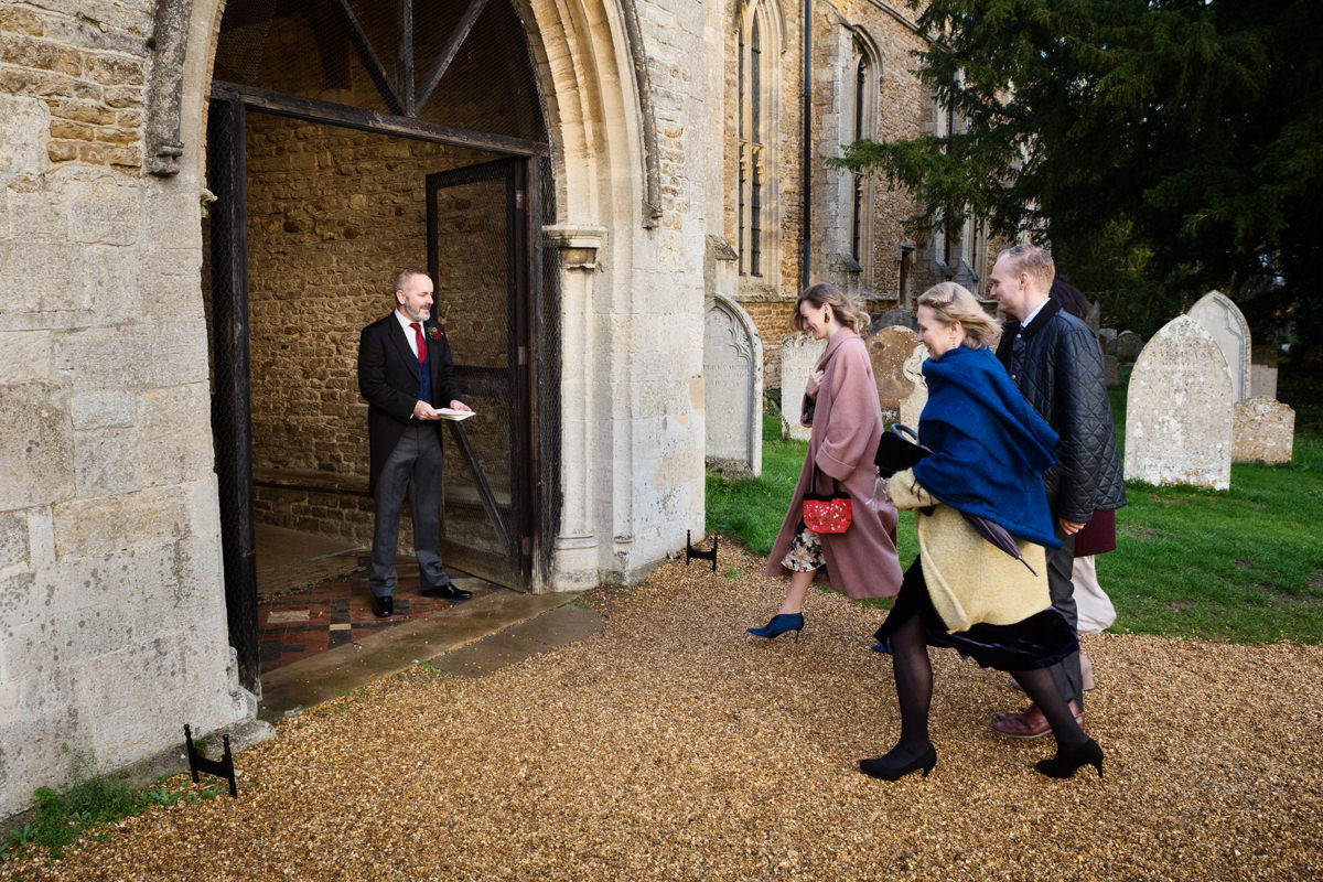 Wedding guests walking into St Andrew's church in Swavesey, Cambridge