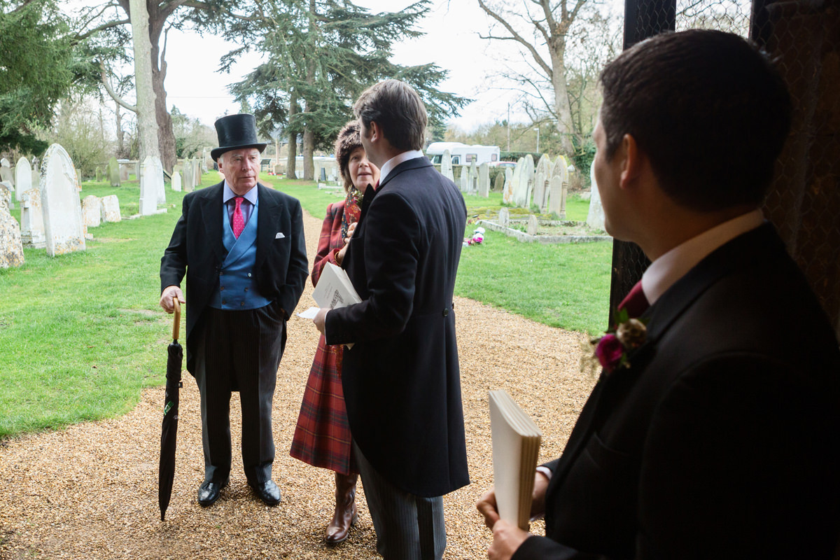 Ushers greeting wedding guests at St Andrew's church in Swavesey, Cambridge