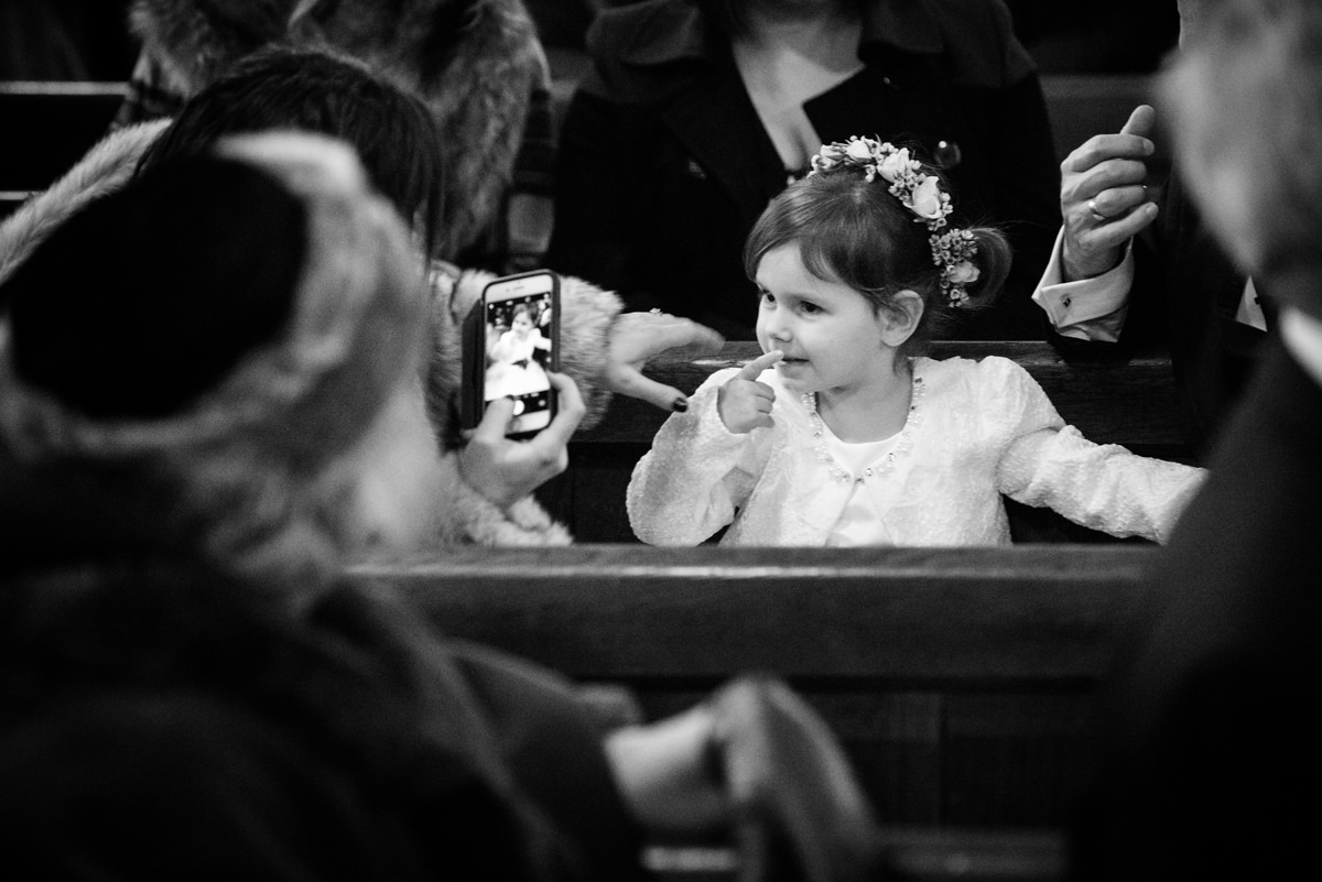 Guest taking a photo of a flower girl at St Andrew's church in Swavesey, Cambridge