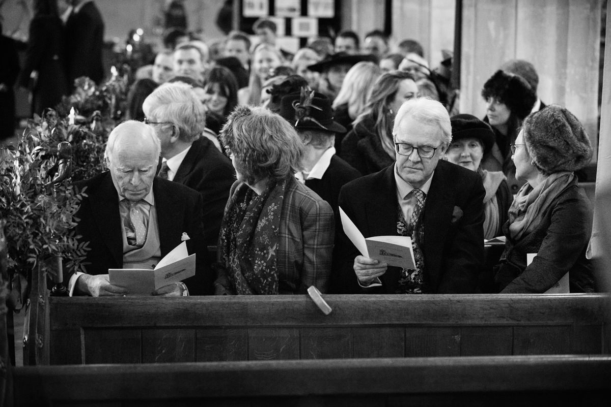 Wedding guests looking at their order of service at St Andrew's church in Swavesey