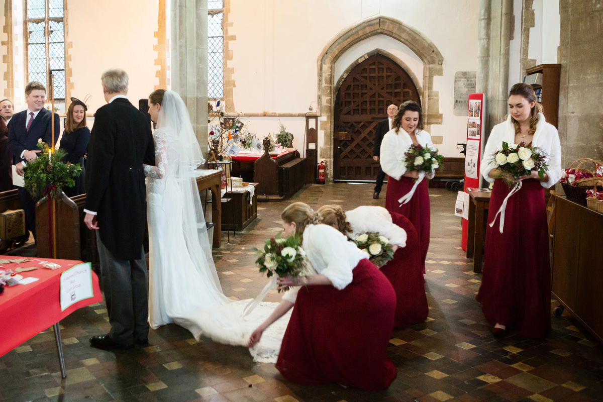 Bridesmaids arranging the bride's train before she walks down the aisle