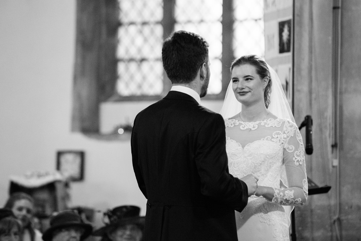 Bride and groom making their vows at St Andrew's church in Swavesey, Cambridge
