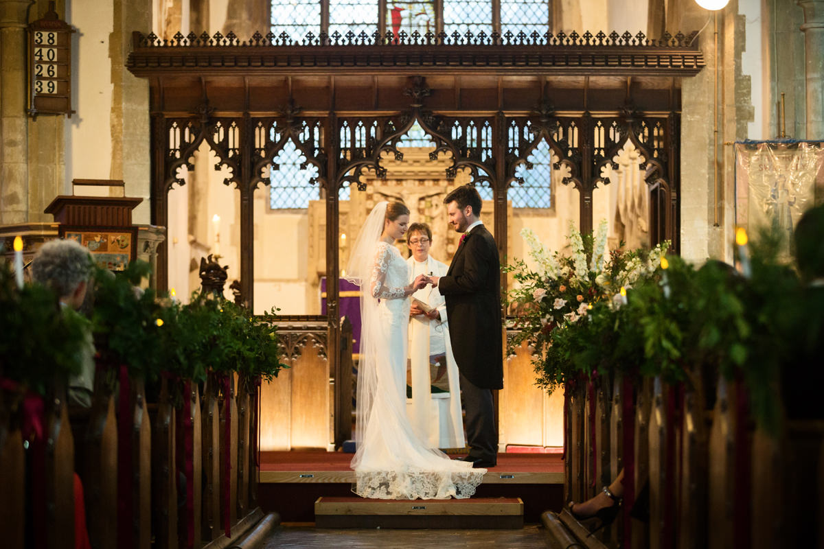 Bride and groom exchanging rings at St Andrew's church in Swavesey, Cambridge