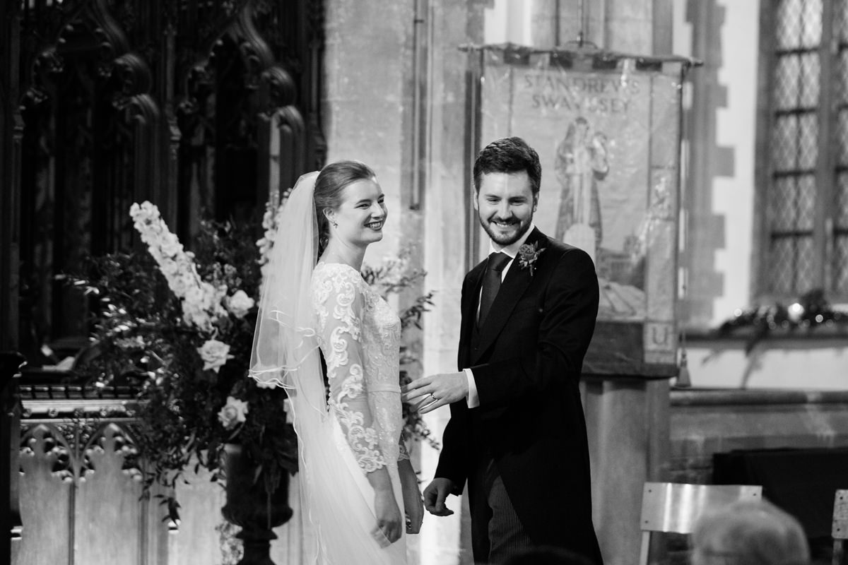 Bride and groom looking at their guests at St Andrew's church in Swavesey