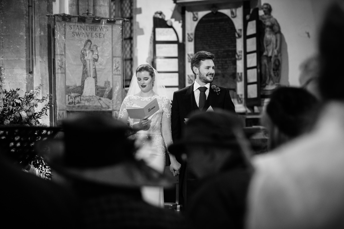 Bride and groom singing hymns at St Andrew's church in Swavesey, Cambridge