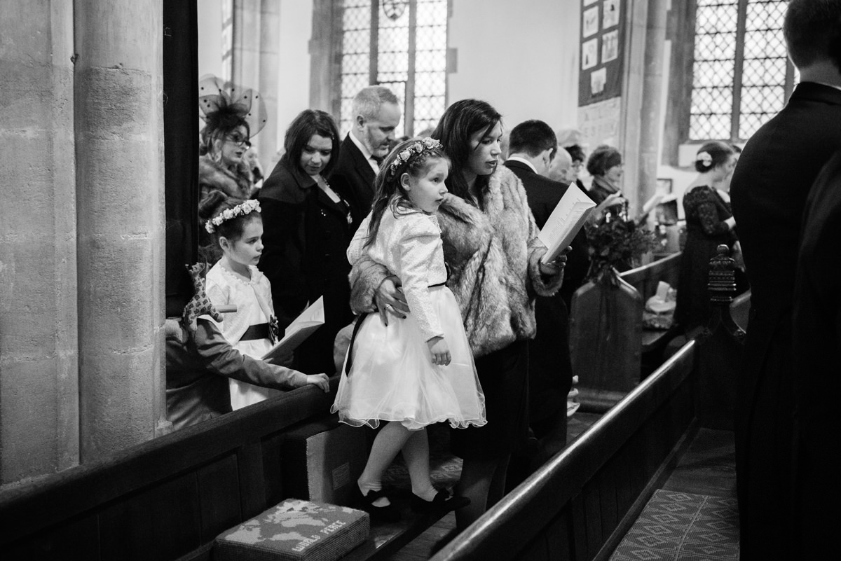 Flower girl standing on a pew at St Andrew's church in Swavesey, Cambridge