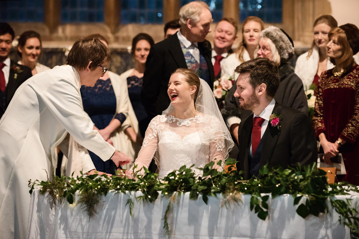 Bride laughing during the signing of the register at St Andrew's church in Swavesey