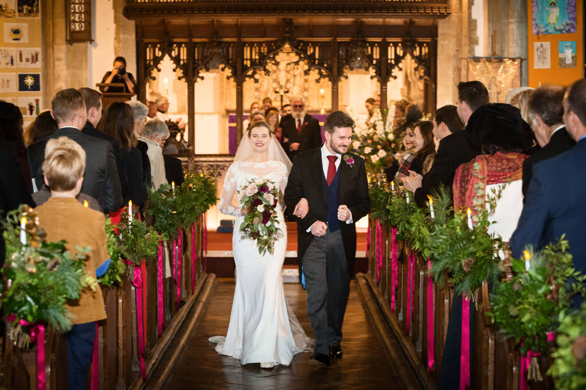 Bride and groom walking down the aisle at St Andrew's church in Swavesey