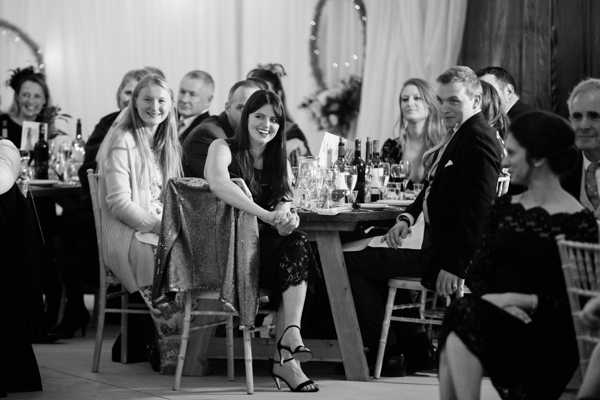 Wedding guests laughing during the speeches in Swavesey, Cambridge