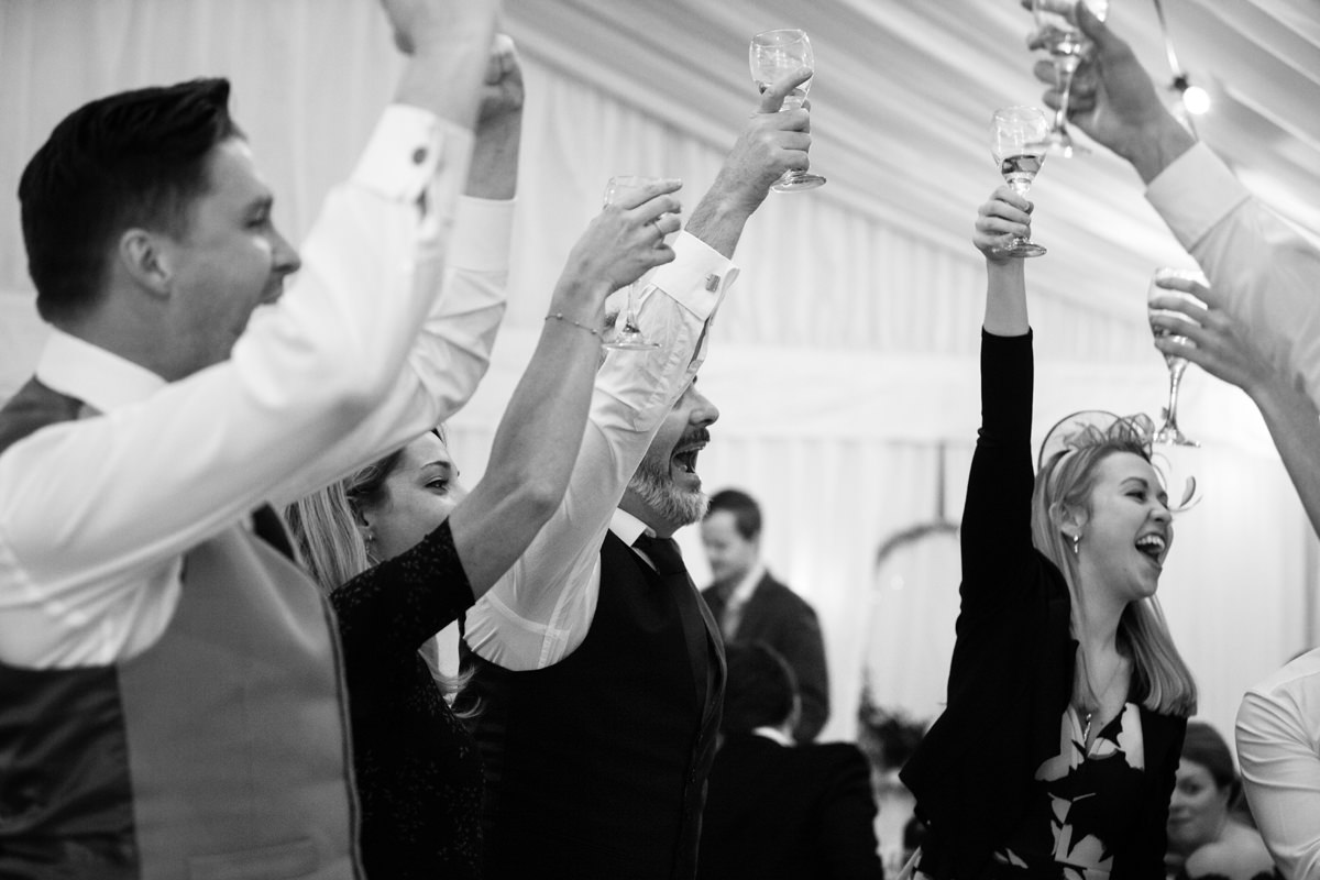 Wedding guests holding their glasses high for a toast at wedding in Swavesey, Cambridge