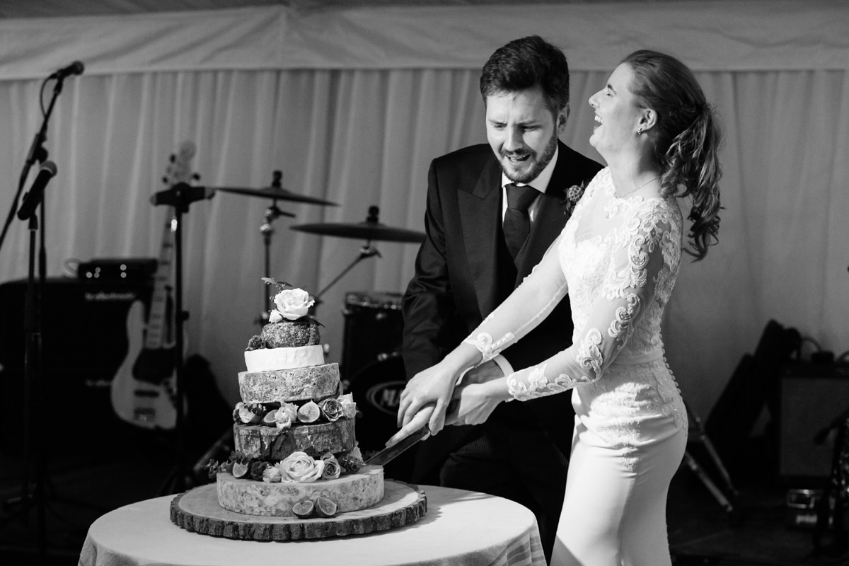 Bride and groom struggling to cut the cheese cake at their wedding in Swavesey, Cambridge