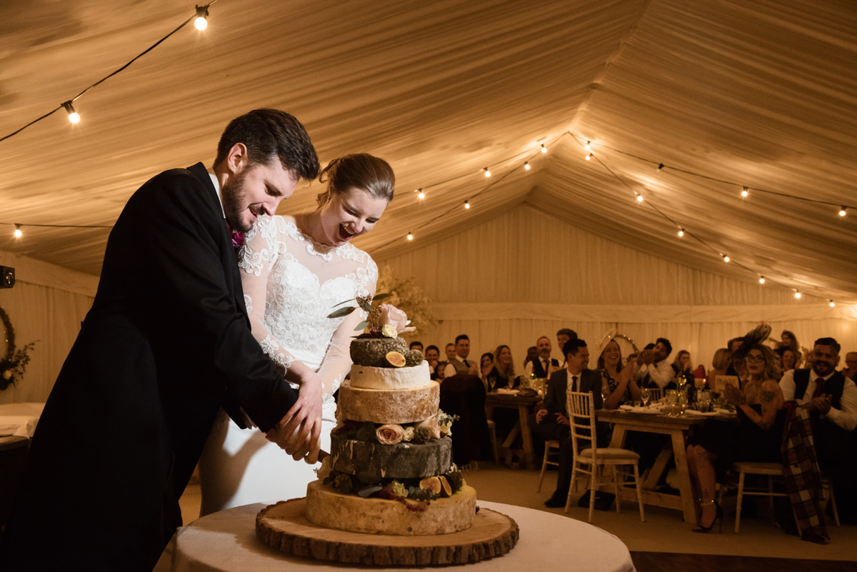 Bride and groom cutting a cake of cheese at their wedding in Swavesey, Cambridge