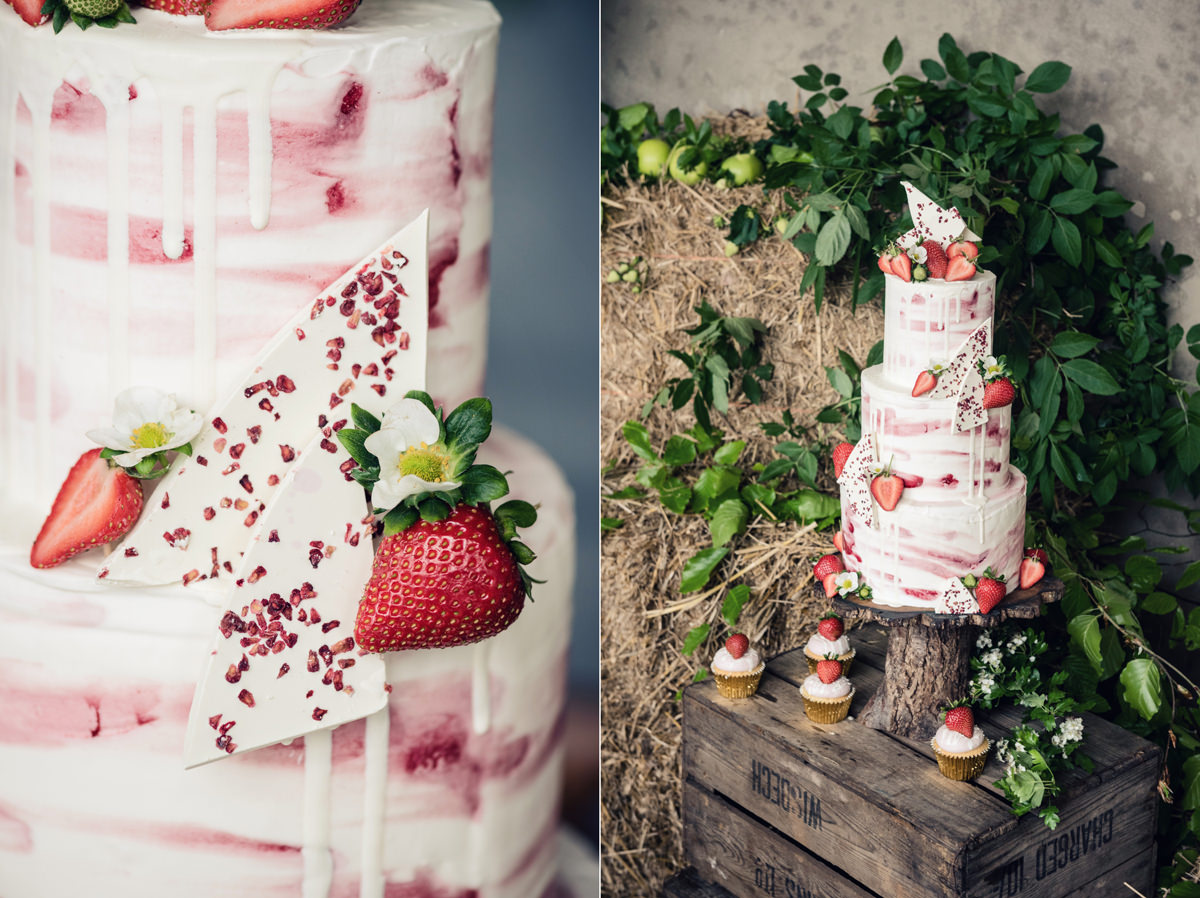 A rustic strawberry themed drip wedding cake with chocolate bark by Couture Cakes