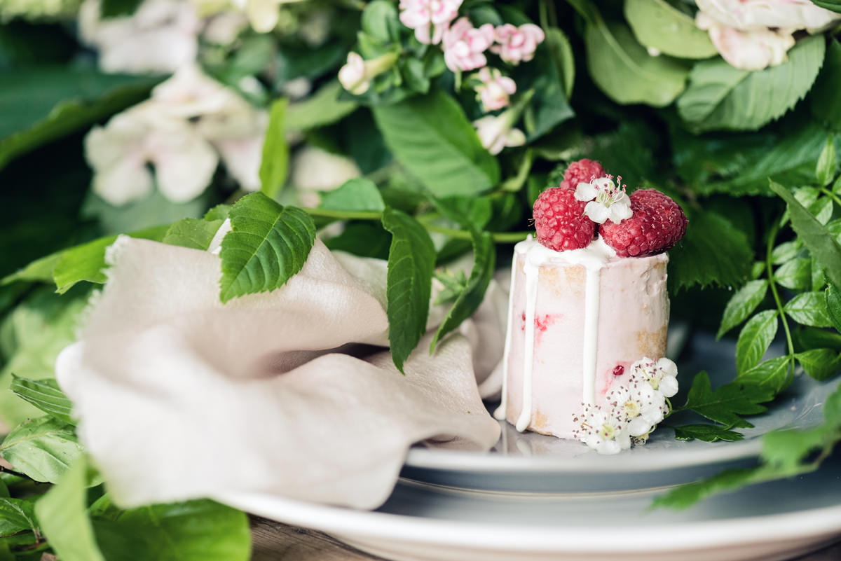 A mini semi-naked drip wedding cake topped with raspberries by Couture Cakes