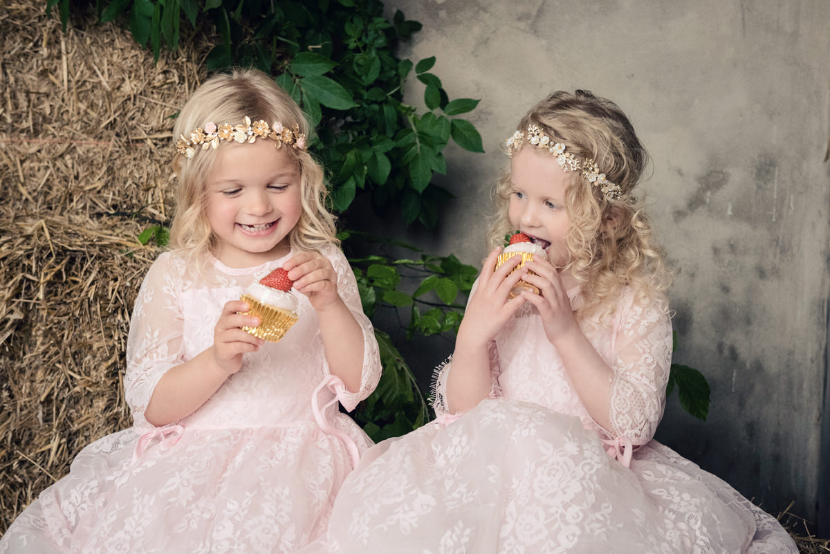 Two flower girls eating strawberry themed wedding cupcakes made by Couture Cakes