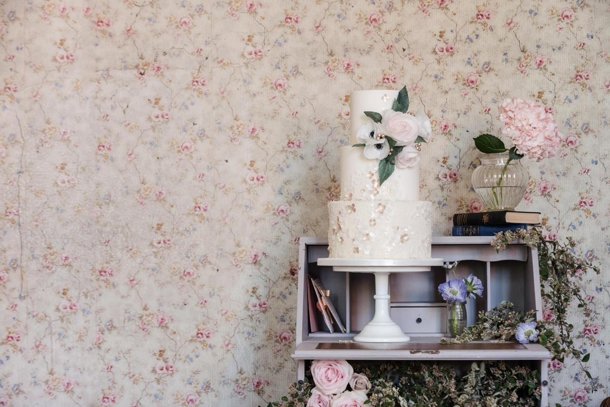 An ethereal romantic wedding cake with wafer paper flowers displayed on a writing bureau