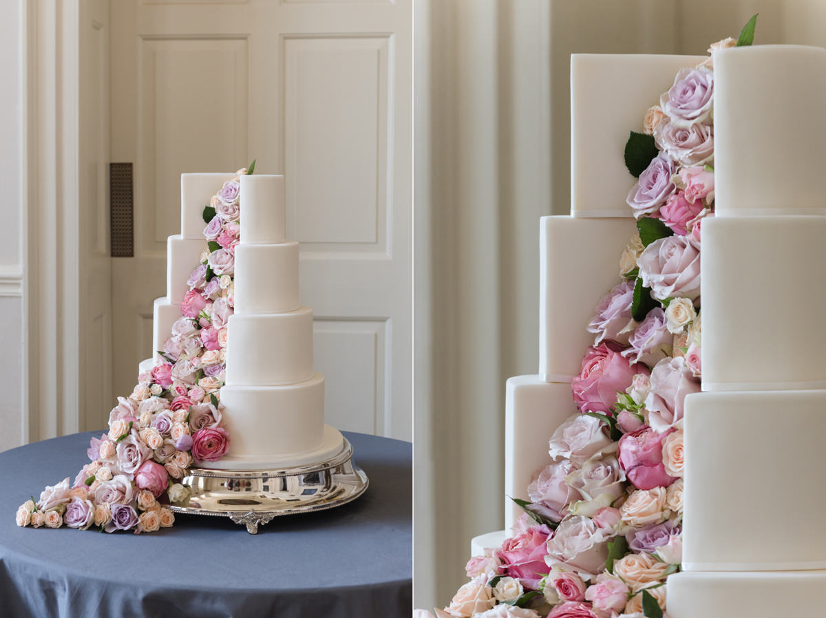 A white wedding cake with fresh flowers tumbling out of it by Couture Cakes