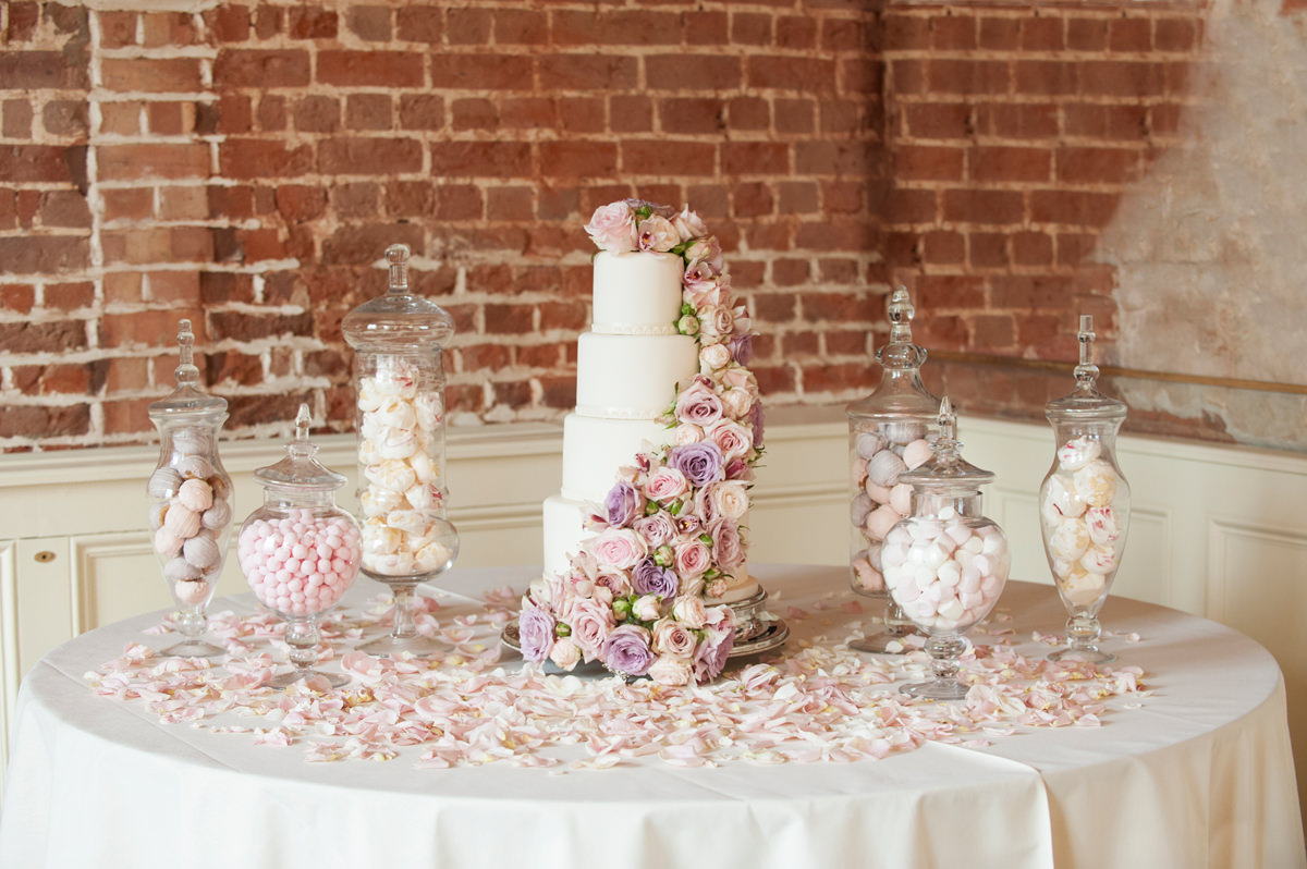A classic white wedding cake with cascading fresh flowers and apothecary jars of sweet treats at Boughton House