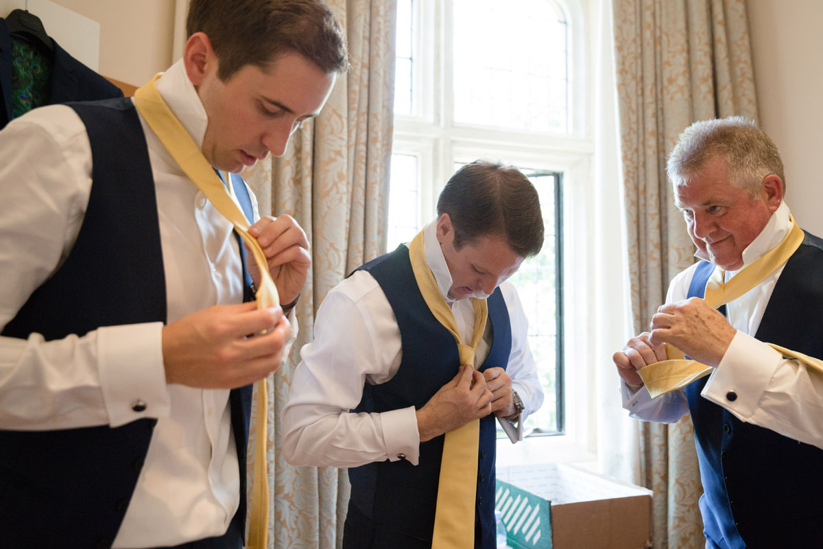 Groomsmen tying their ties at Notley Abbey