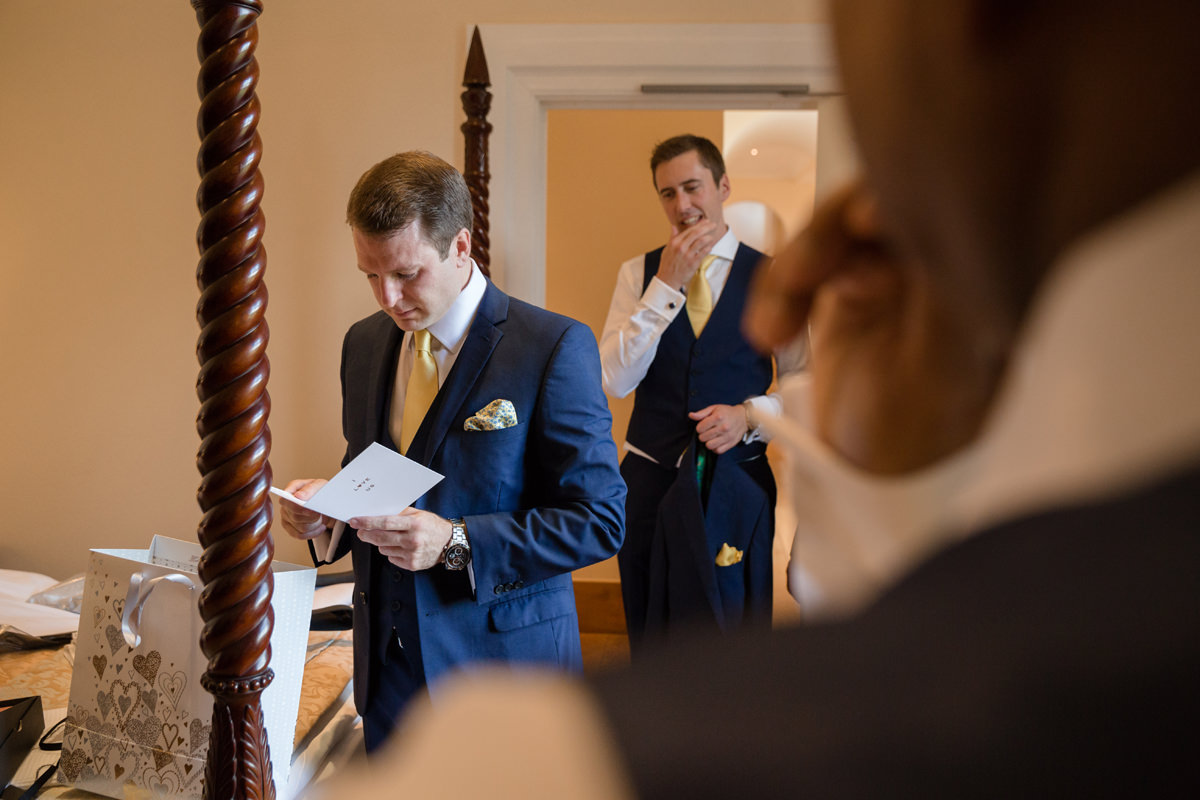 Groom reading wedding day card from bride at Notley Abbey